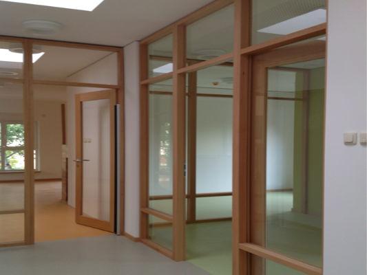 Raumteiler aus Glas mit Holzverkleidung und Türen