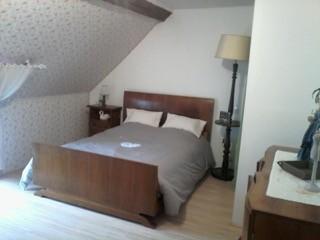 Chambre rose qui comprend un lit deux personnes et un lit d'appoint