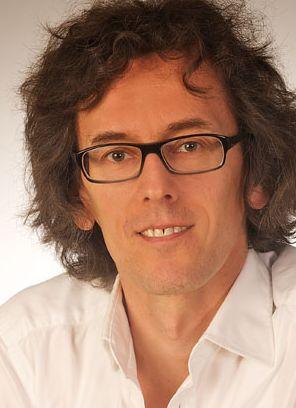 Portrait von Psychologen Klaus Pötzlberger, Wien: er lächelt ins Bild und hat eine gesunde Frabe. Er trägt braunes, mittellanges Haar, hat braune Augen und trägt eine Brille.
