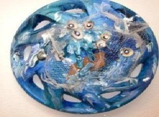 Radkappe kreiert mit Muscheln, Perlen, Fischernetzen und ein Ruderboot.