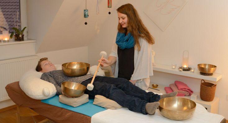 Ein Kind liegt in Rrückenlage auf der Massageliege. Dabei steht eine kl. Beckenschale am Solarplexus, eine Gelenkschale auf der rechten Handinnenfläche und eine gr. Beckenschale vor den Füßen.