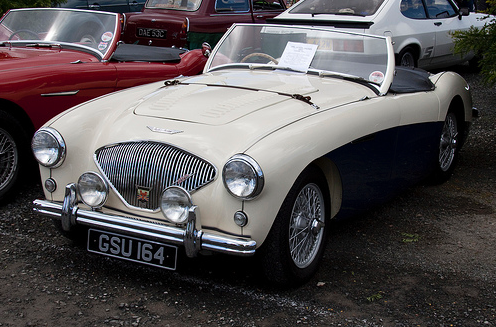 1955 Austin-Healey 100M. Redzamākā Austin-Healey 100M atšķirība bija pazemināts motora pārsegs ar ādas siksnu pāri pārsegam. Citiem modeļiem šī paka bija par papildus samaks vai iekļauta pasūtot Le Mans paku. 100M bieži tika pasūtīts divos krāsu toņos…
