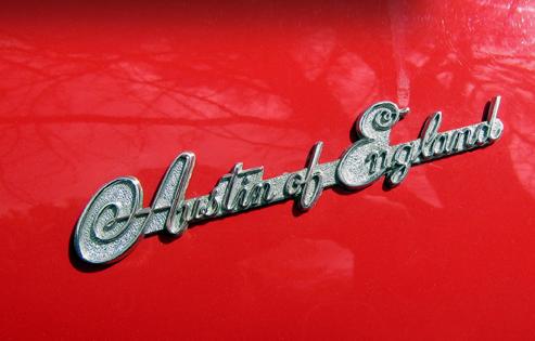 "1953 Austin-Healey 100, aizmugures logo. Pirmos 100tos aizmugurē rotāja logo""Austin of England"", kas 1954 gada vidū tika nomainīts uz Austin Healey logo."
