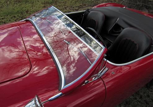 1953 Austin-Healey 100 priekšējais logs. Orģinālais Austin-Healey 100's nolaižamā priekšējā stikla ideja bija Donalda Healeja lolojums, kas Kokeram bija jāieviešs dzīvē.