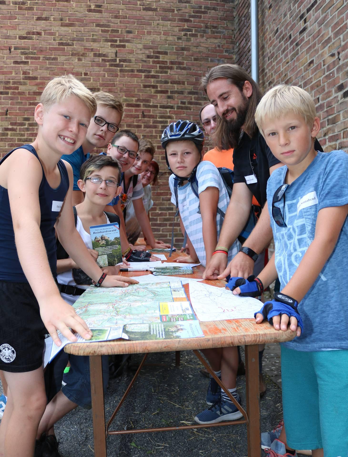 """Beim Thema """"Fahrrad"""" lernen die Kinder vor der Tour die Technik der Räder kennen und kleine Reparaturen selbst durchzuführen. Mit dem Radverkehrsbeauftragten des Landreises, Stefan Arend, wurden die Karten studiert."""