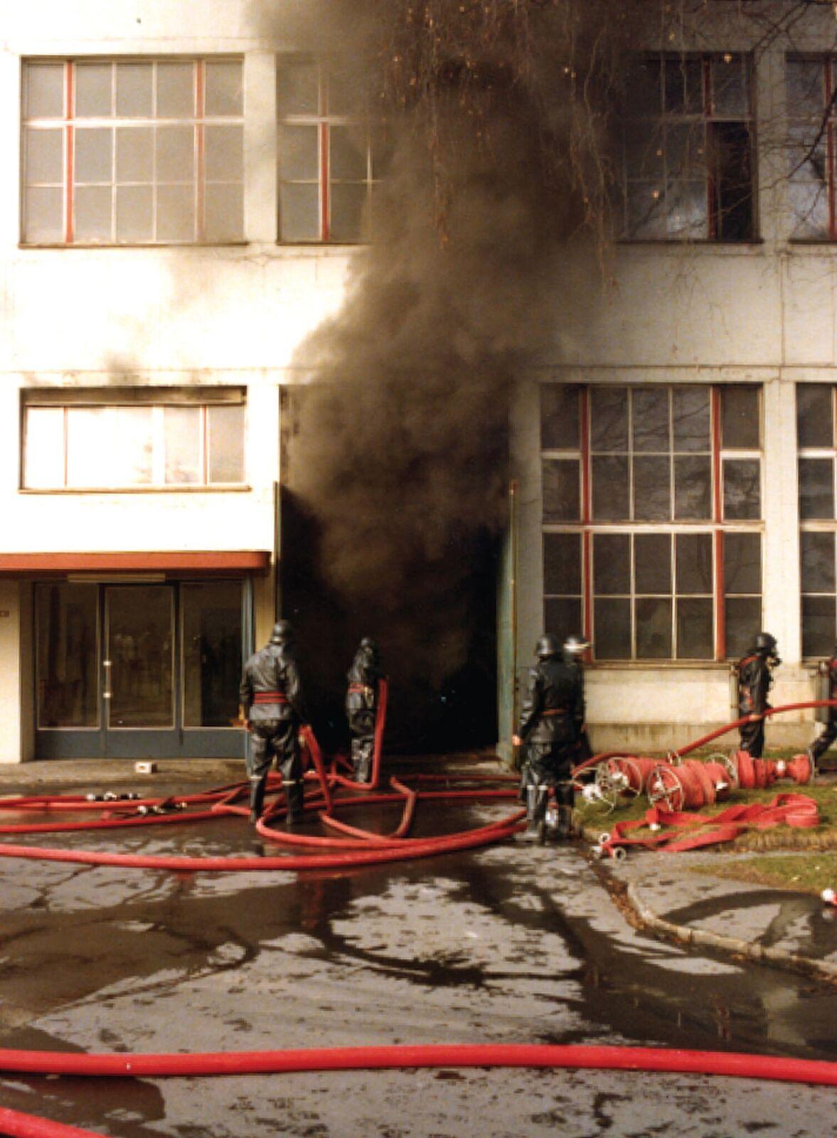 Schwarzer Rauch quillt aus dem Fabrikationstrakt ins Freie.