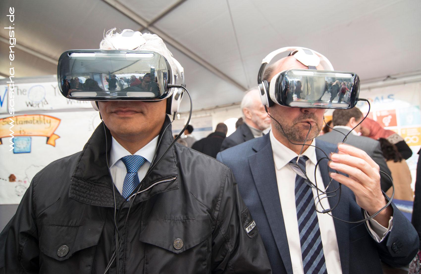 Bonns Oberbürgermeister Ashok Sridharan (links) und Minister Franz-Josef Lersch-Mense (rechts) probieren Virtualle Brillen am Stand des United Nations System Staff College aus.