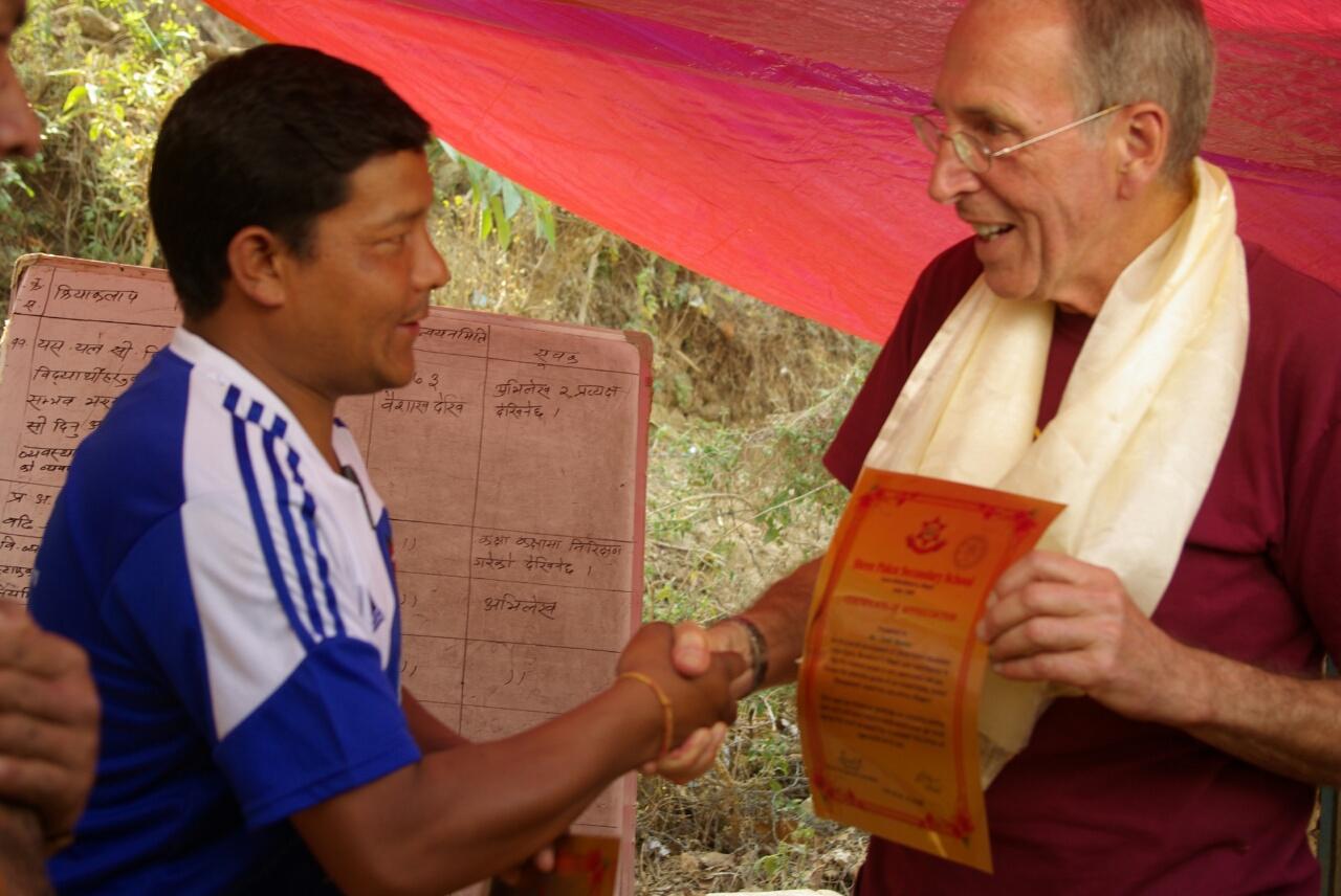 Binaya Lama, der Vertreter der Gemeinde, überreicht die Urkunden.