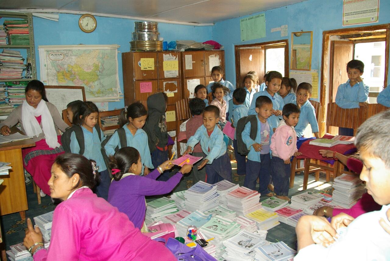 Die Kleinen bekommen Hefte und Stifte einer Hilfsorganisation.