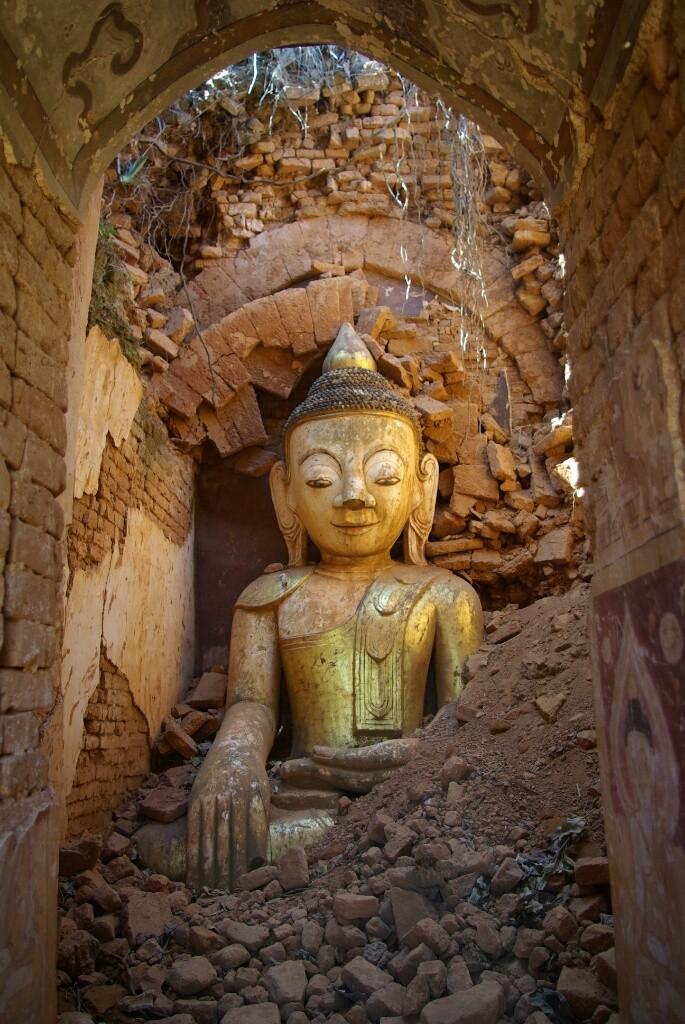 Ein lächelnder Buddha in einer zerfallenen Pagode.
