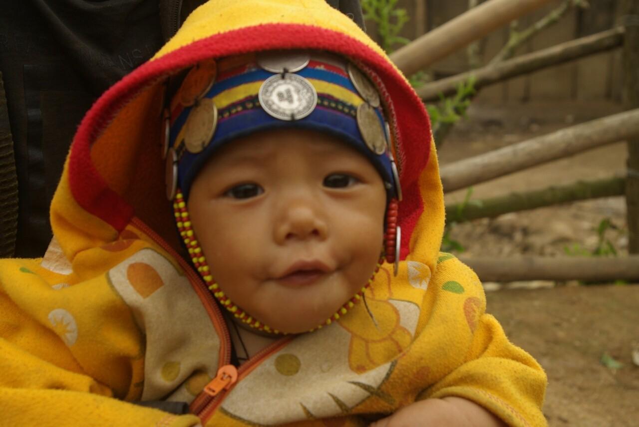 Das Baby trögt schon den typischen Schmuck der Akha.