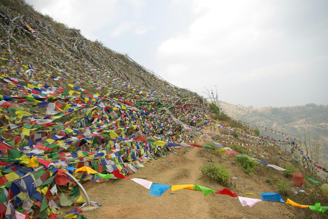 Mit Gebetsfahnen überzogener Hügel