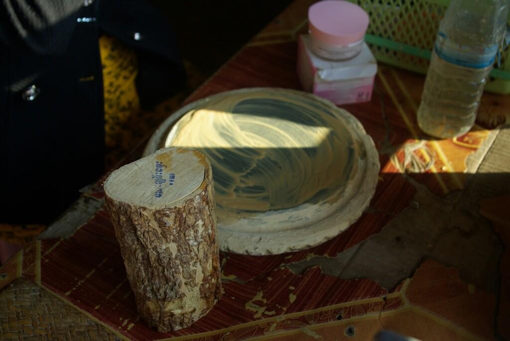 Thanaka: Die Rinde eines Holzstückes vom Holzapfelbaum wird mit etwas Wasser auf einem Steinteller abgerieben..