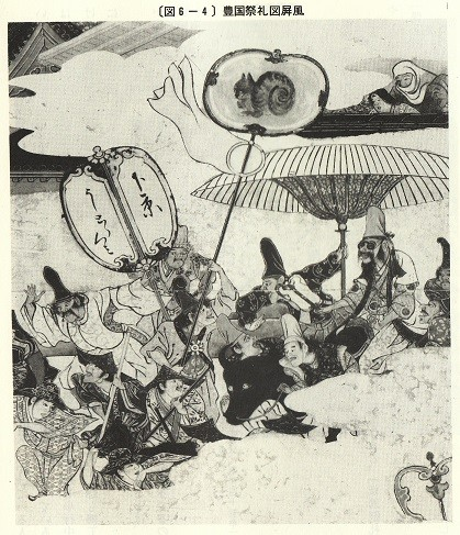 傘の下、右側にいる人物が眼鏡を掛けている。仮装行列の様子。