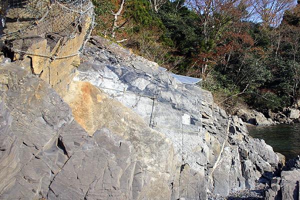 岩の表面にアクリル板をかぶせて保護している
