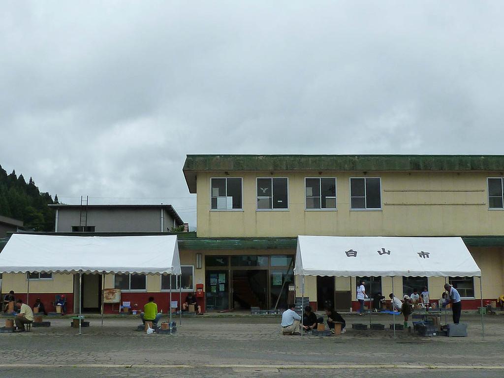 調査センターの前にテント。21日は曇り時々雨。センターの軒下でたたく方も。