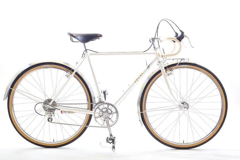 Aさんのツーリング車: コルナゴのロードレーサーで颯爽とオーダーにいらっしゃったAさんのご注文は、「白と黒だけで構成された、美しい自転車」。かつて憧れたサンツアー・シュパーブプロの変速機でデュラエースの10段スプロケットを動かし、さらにペダルは学生時代にお使いになられていたものをチューニングして装着しました。ご満悦のAさんは「アプレ号は、自分の部屋に飾って、もちろん休みの乗れる日には乗って、たまには遠出して、これから楽しみたいと思います」と話して下さいました。フレームカラーは「パール」です。