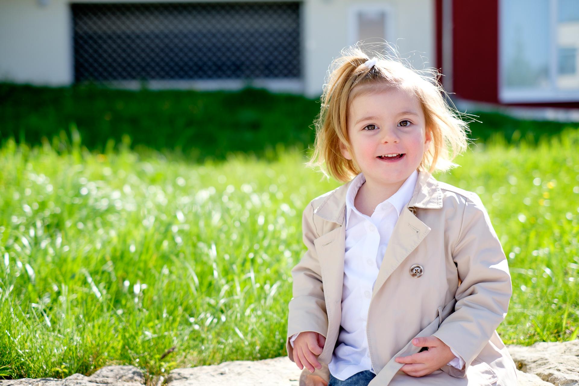 Hübsches Kind auf Mauer fröhlich
