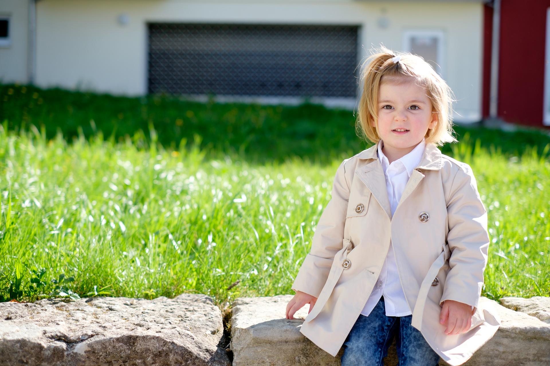 Kinderportrait Kind im Trenchcoat auf Mauer