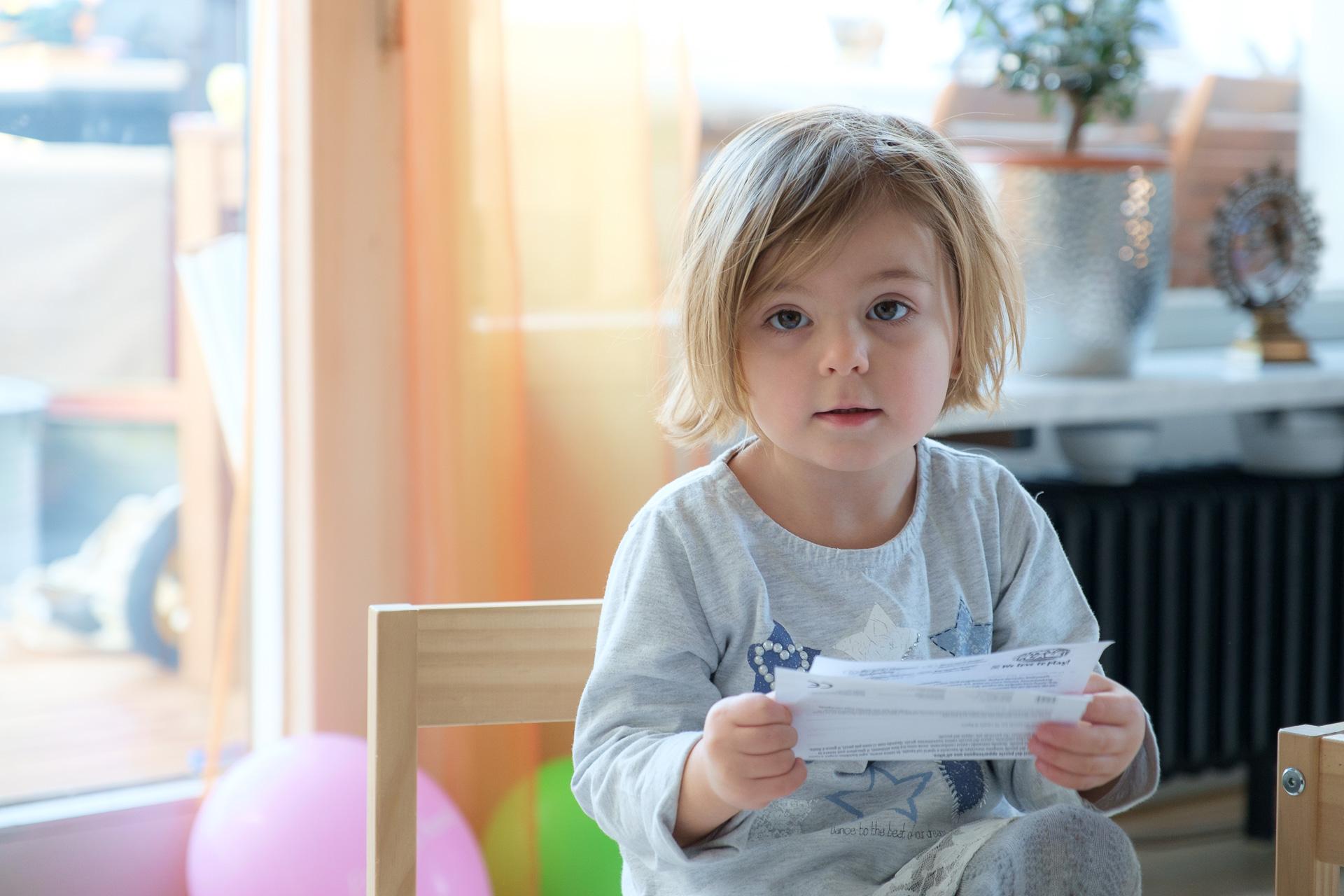 Kind auf Stuhl mit Papier in der Hand