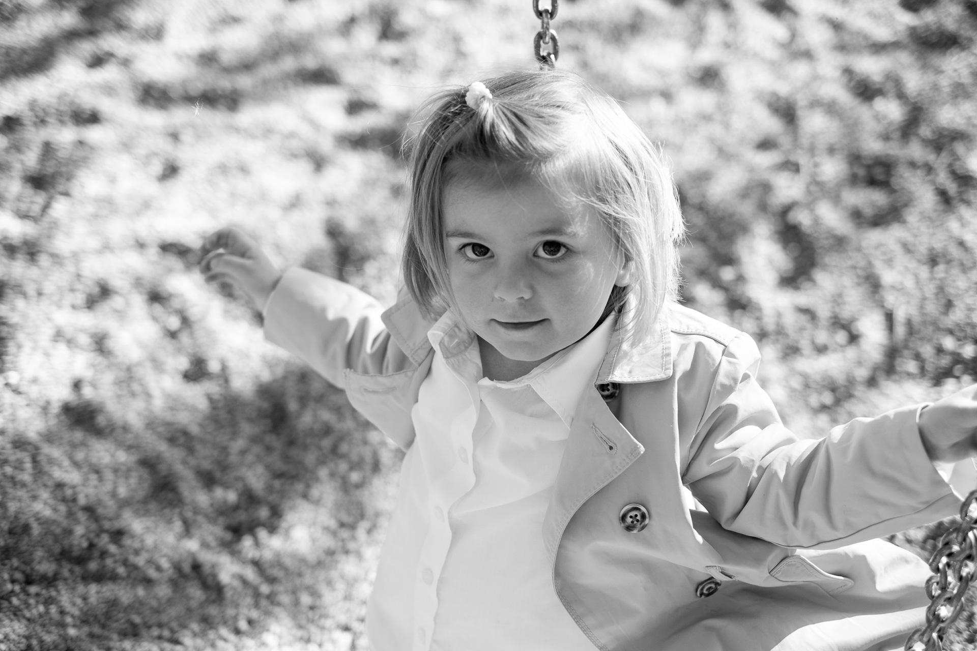 Kind im Trenchcoat an der Schaukel