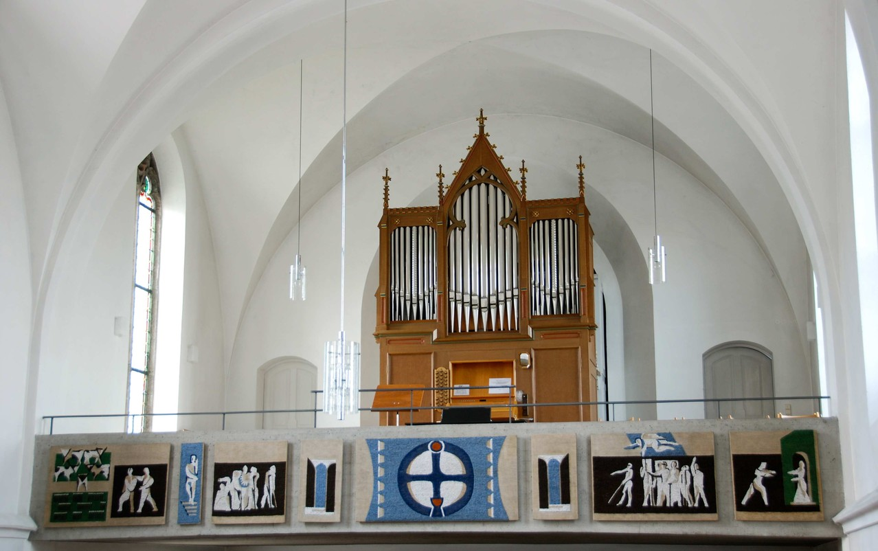 Die Orgelempore. Die Brüstung wurde 1979 mit einem vom Frauenkreis gestickten Bilderfries verschönt. 1985 wurde von der Firma Hey aus Ostheim v. d. Rhön aus der alten Orgel eine neue mit drei Manualen und 24 Registern mit romantischer Klangfärbung gebaut.