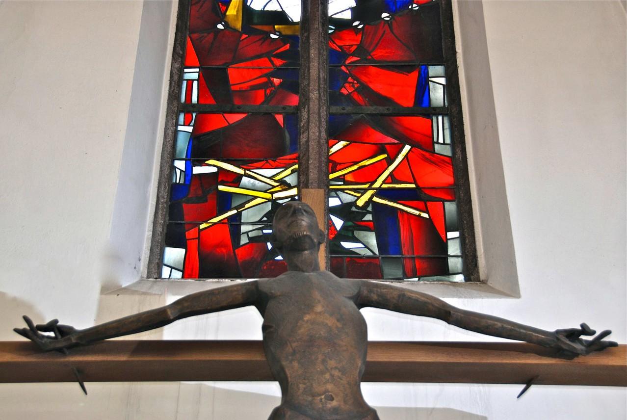 Das bronzene, überlebensgroße Kruzifix wurde von Rolf Nida-Rümelin (geb. 16.06.1919. gest. 26.10.1996) geschaffen. Hier ist Jesus nicht nur als der Gekreuzigte, sondern zugleich als der zu Gott erhöhte Herrn dargestellt.