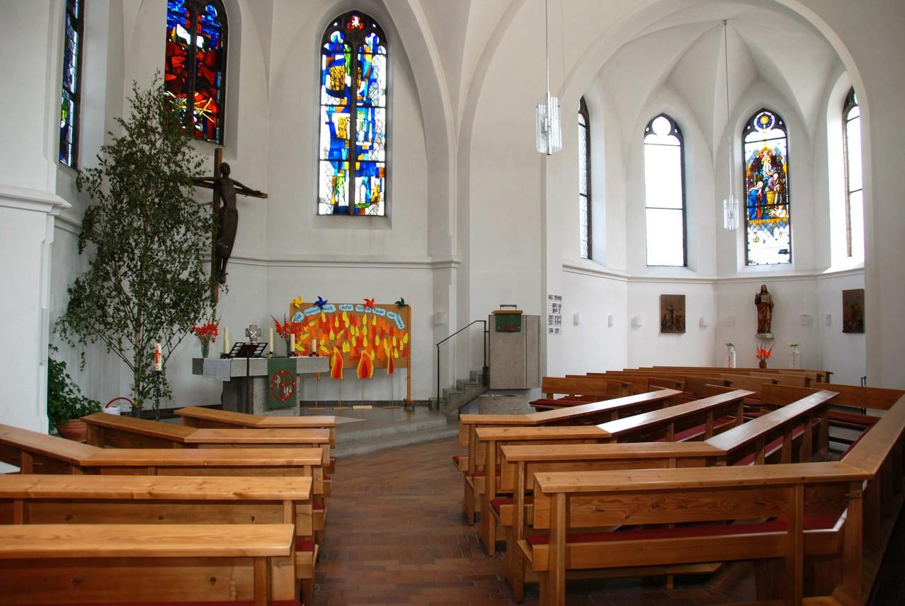 Blick vom  Eingang auf den ehemaligen Altarraum im Osten und links der 1964/65 geschaffene neue Altarraum im nördlichen Seitenchor mit Kanzel. Die Bänke sind kreisförmig, mit Blick auf den neuen Altar, ausgerichtet.
