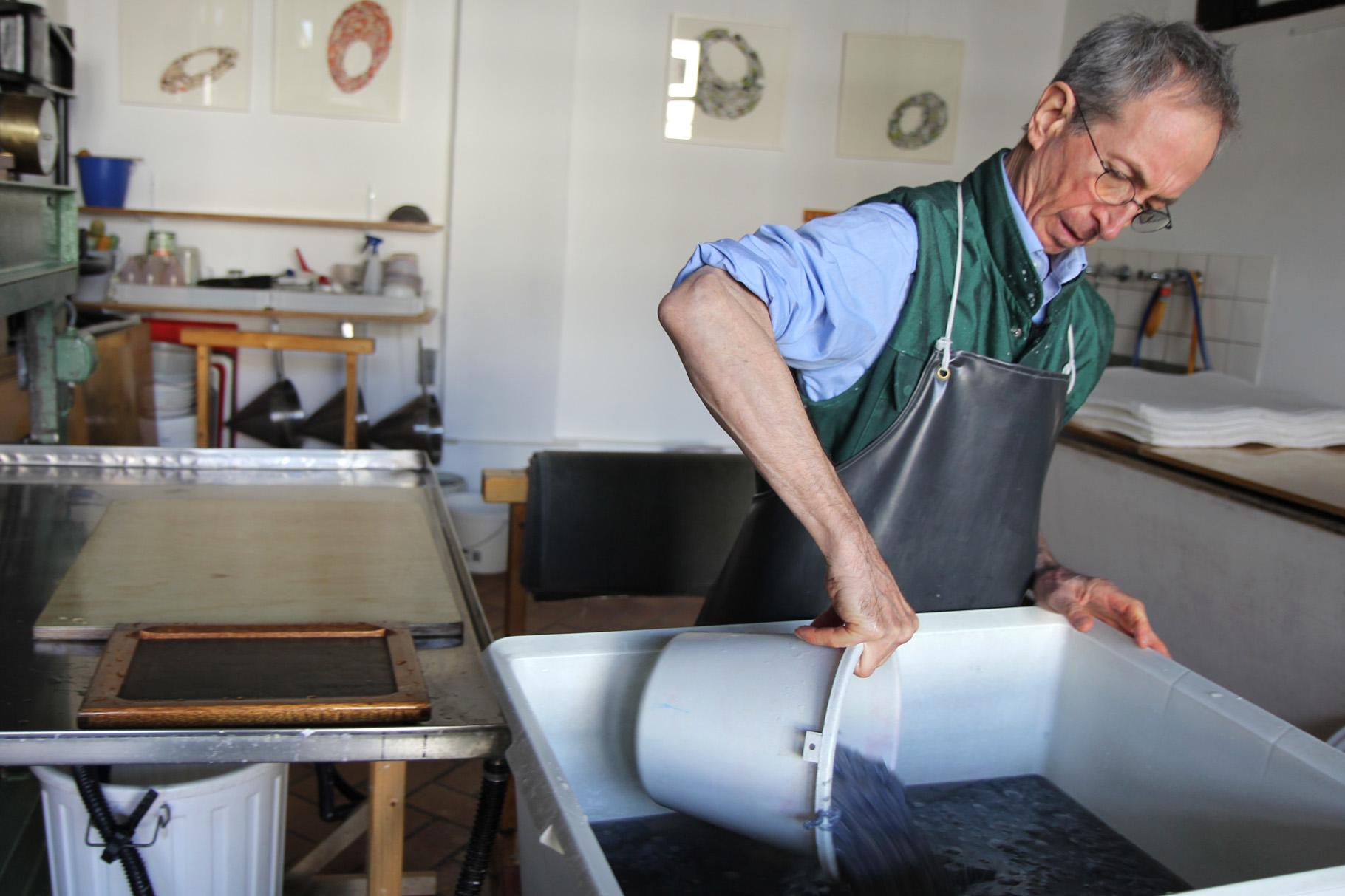 John Gerard füllt den fertig geschlagenen Faserbrei in die mit Wasser gefüllte Bütte...
