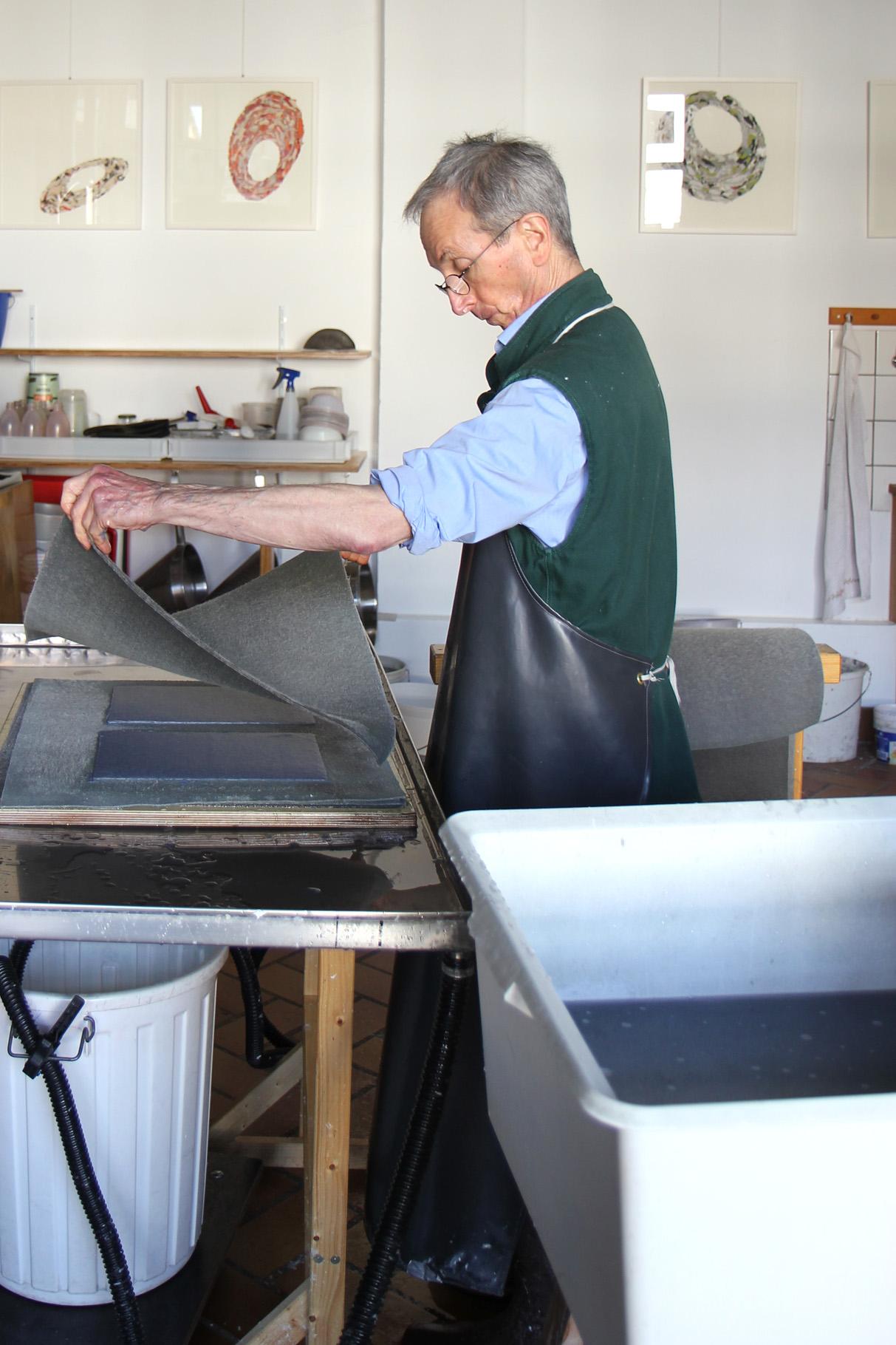 John Gerard deckt die gegautschten Bogen mit einem weiteren nassen Filz ab