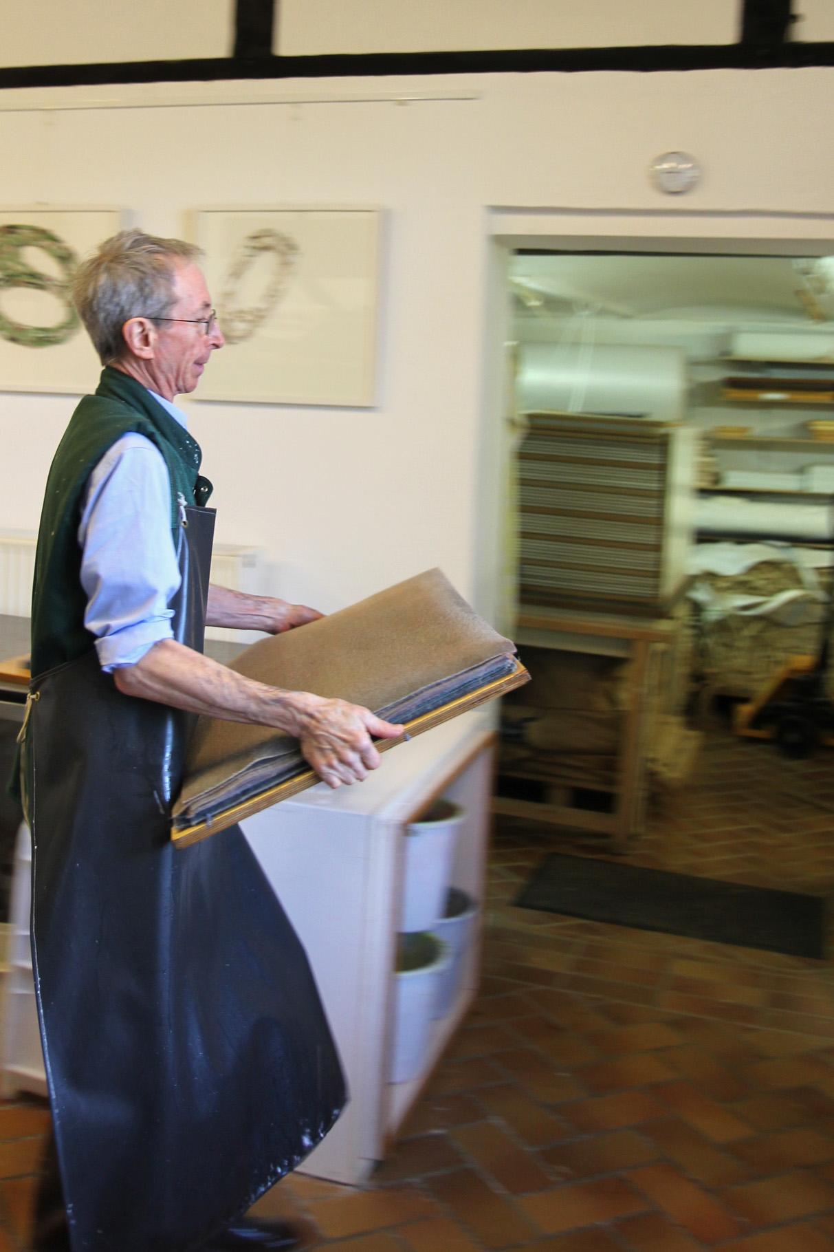 Nachdem ein Stapel aus geschöpften Bogen und Filzen entstanden ist, trägt John Gerard diesen Pauscht zur Presse...
