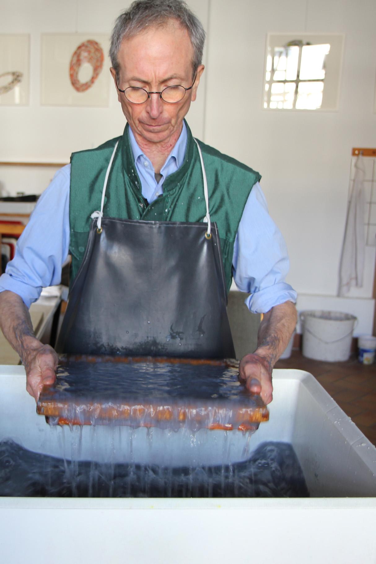John Gerard schöpft einen Bogen echtes Hadernpapier von Hand aus der Bütte