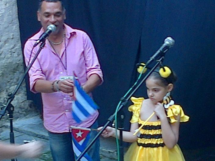 Una niña cubana, entregando la bandera de Cuba a los invitados internacionales junto al director del Encuentro, Osvaldo Perez Peñalver. Esa bandera preside mi escritorio hoy.
