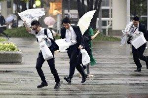 強い風と雨に飛ばされそうになって道路を渡る人々。