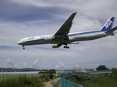 大阪国際空港の南側、千里川沿いで多くのカメラを持った人が着陸する飛行機に夢中