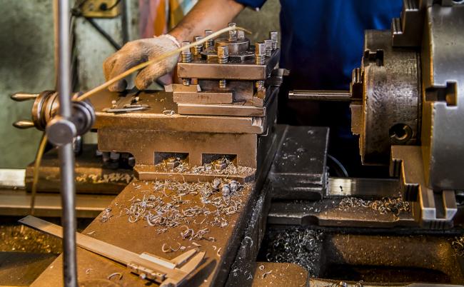 工場の中にある旋盤機が新しい製品を作り出す。