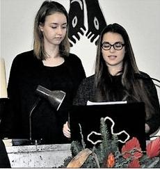 Die KGS-Schülersprecherinnen Nele Fricke (links) und Karina Malarowski erinnern in der Friedhofskapelle auch an die Opfer der Terroranschläge von Paris und Nizza. (Eggers/HAZ)
