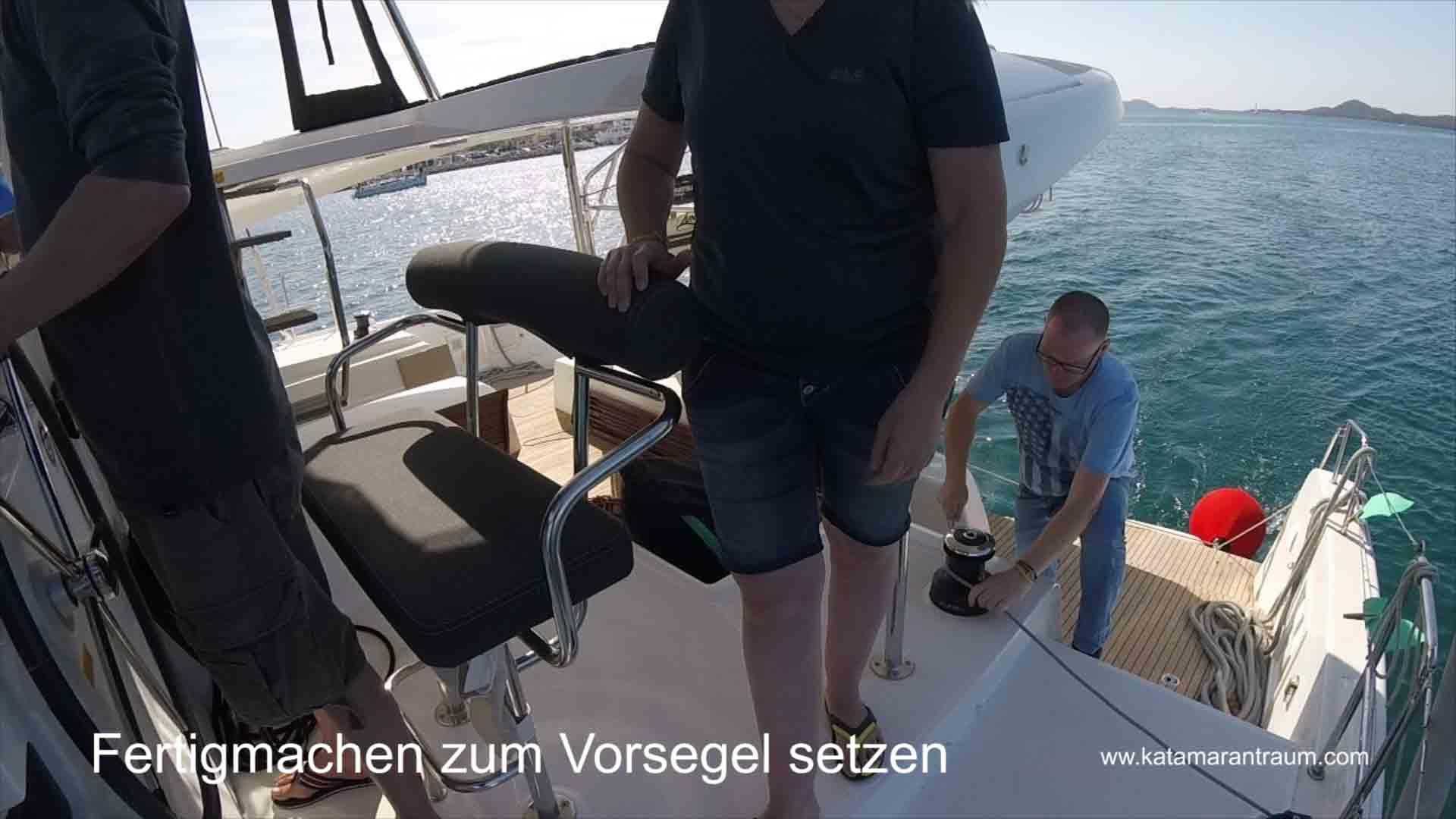 The catamaran training participants set the foresail