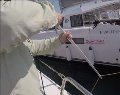 Crewmitglied am LUV-Heckseite nimmt mit Bootshaken die Muringleine auf