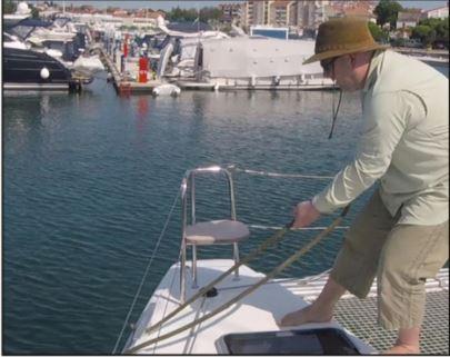 Crewmitglied zieht (unterhalb vom Reling) die Muringleine stramm, und belegt Murlingleine auf die Bugklampe