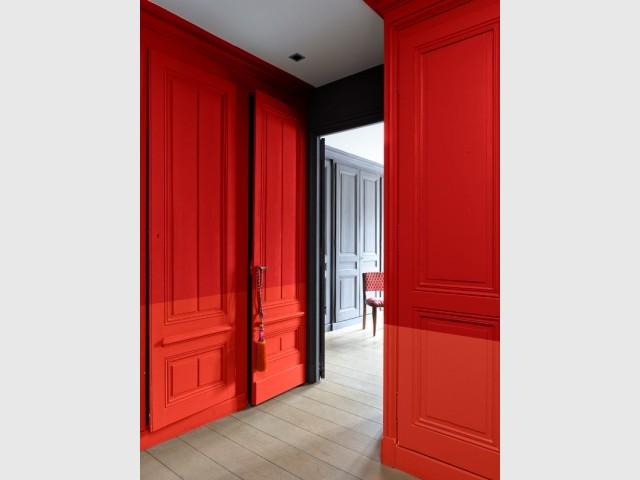 Peinture murale de couleur rouge appliquée sur des menuiseries et des sous-bassements.