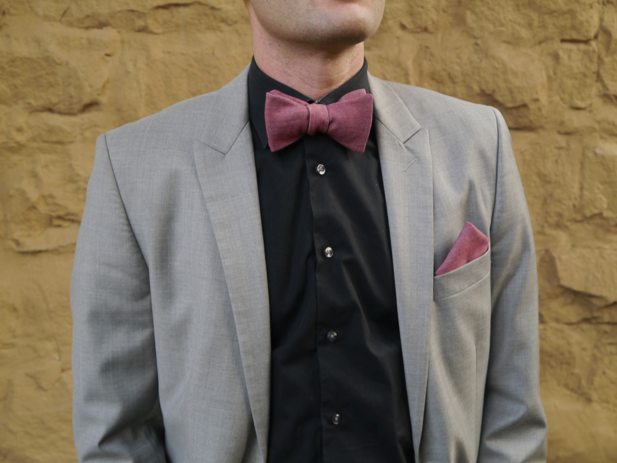 dunkel rose rote fliege auf grauen anzug mit einstecktuch