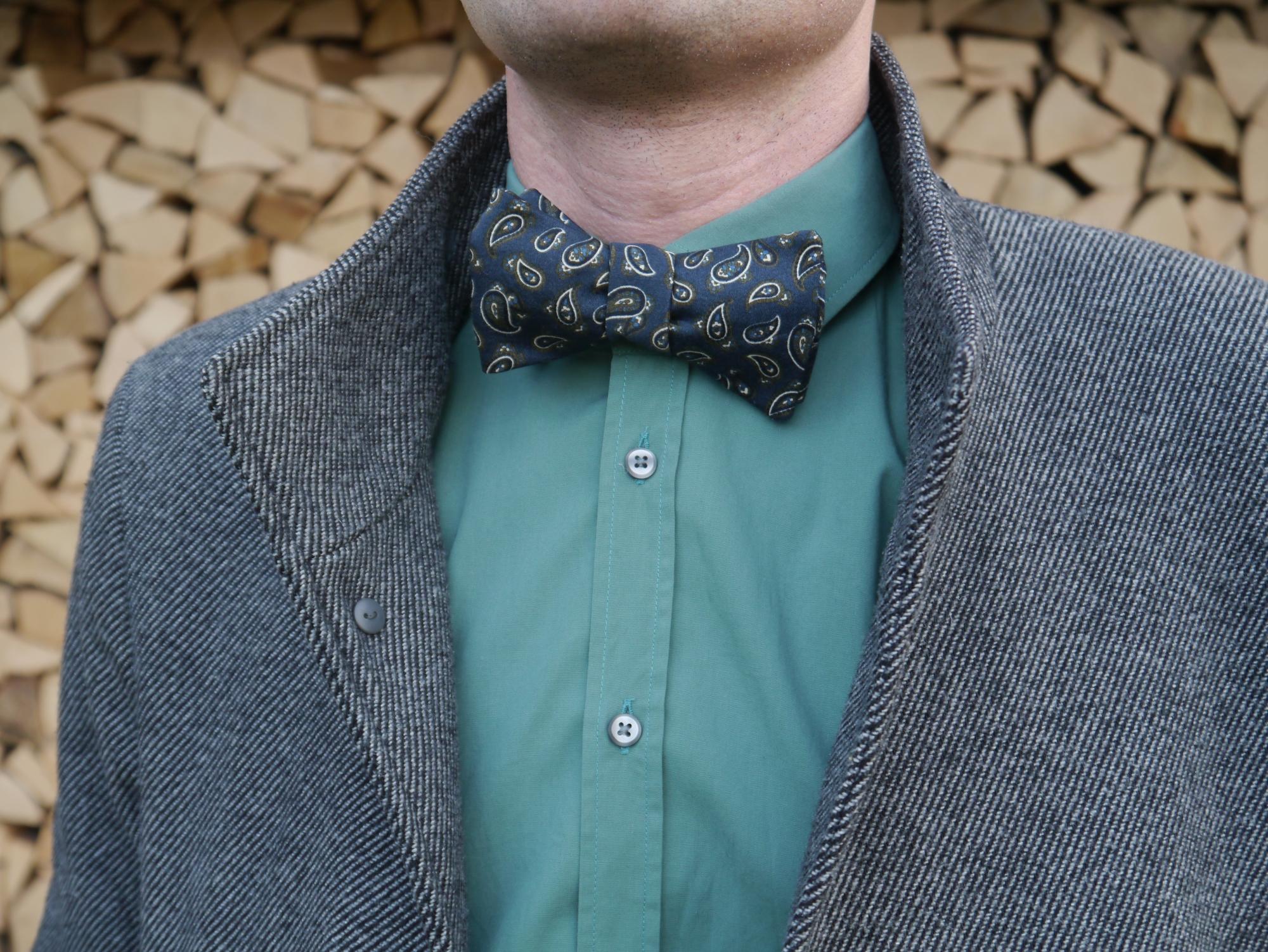 blaue fliege zum selberbinden paisleymuster auf grünes hemd und mantel