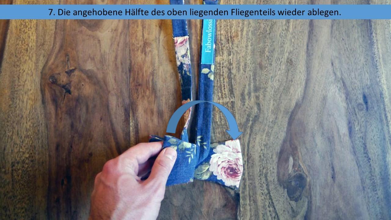 Schritt 7 der einfachen Anleitung zum Fliege binden - Die angehobene Hälfte des Querbinders wieder ablegen
