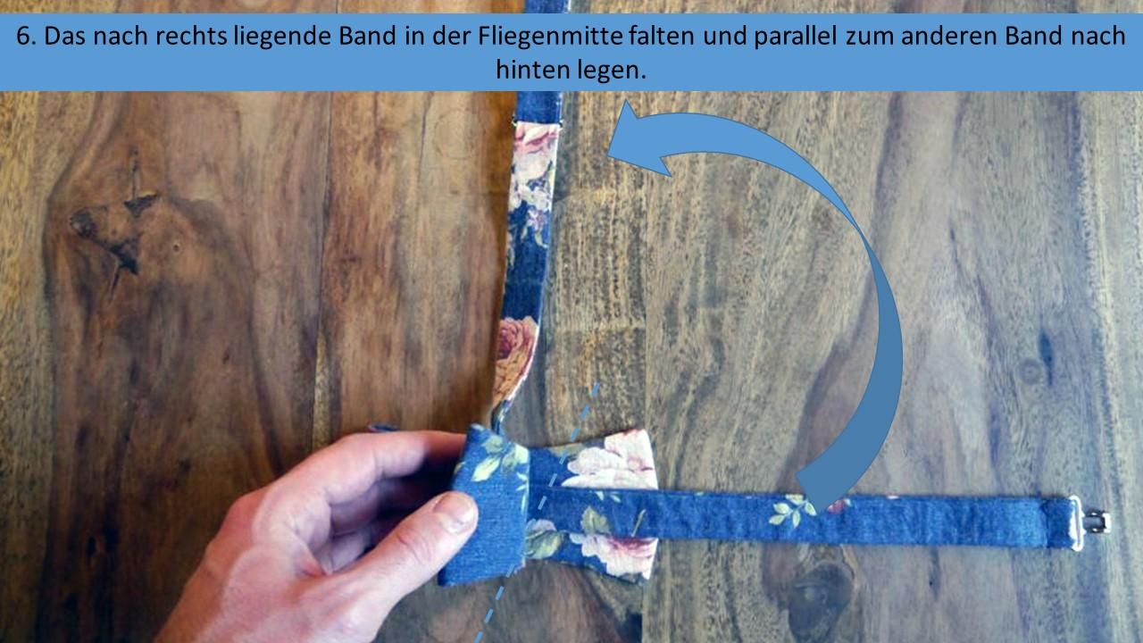 Schritt 6 der Anleitung zum Querbinder binden - Das nach rechts liegende untere Band in der Fliegenmitte falten und nach oben, parallel zum ersten Bändchen legen