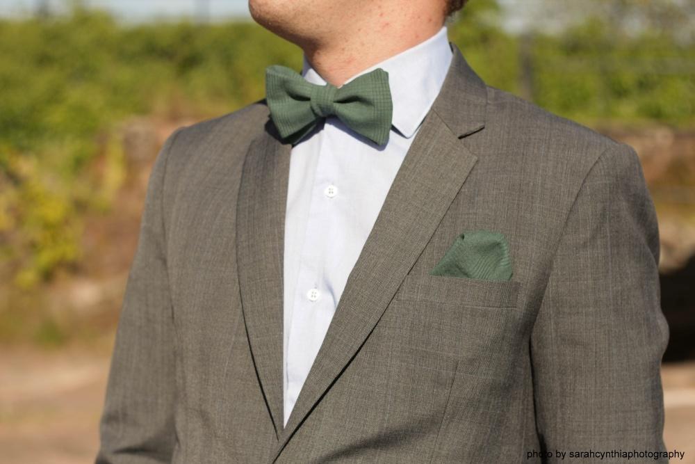 grüne fliege mit einstecktuch auf grauer anzug