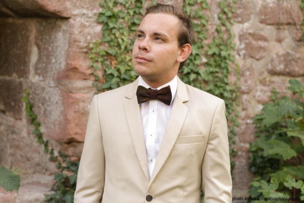 braune rostfarbene fliege zum selbstbinden auf weißes hemd beiger brauner anzug