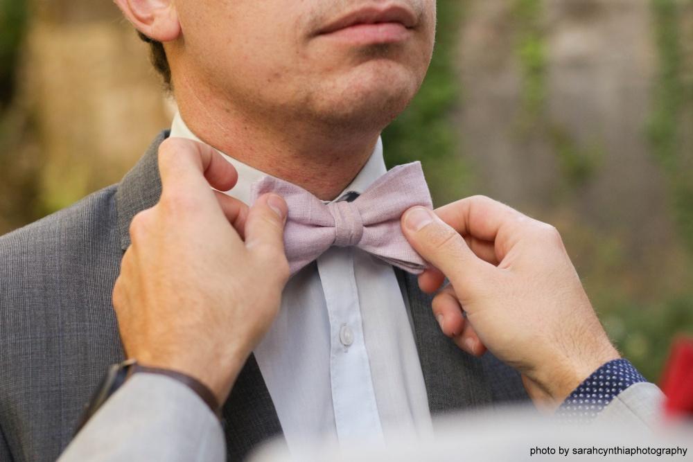 lila Hochzeitsfliege auf grauer Anzug