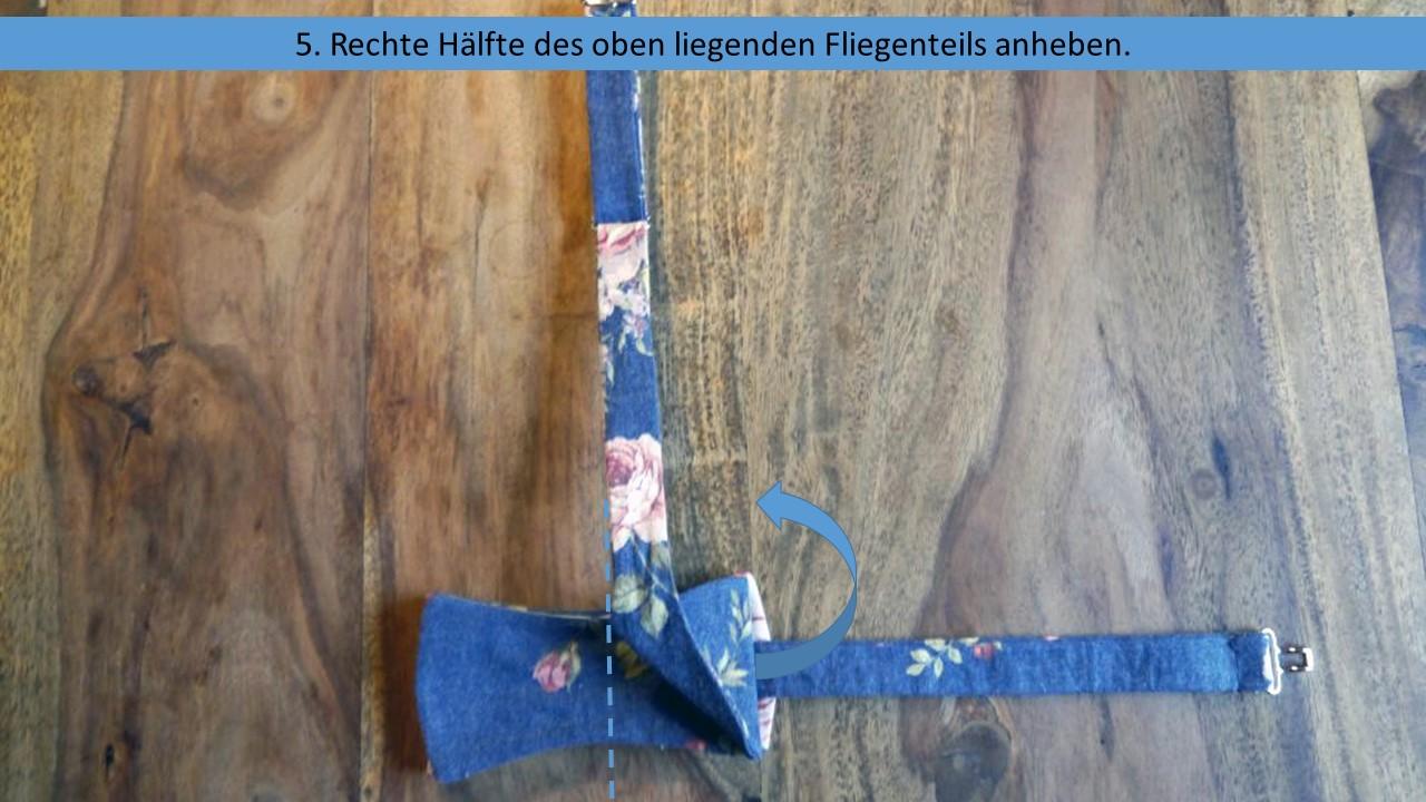 Schritt 5 der vereinfachten Anleitung zum Fliege selberbinden - Die rechte Fliegenhälfte anheben um an das Band darunter zu kommen