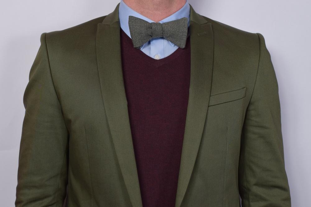 graue fliege zum selbstbinden auf grüner anzug und pullover
